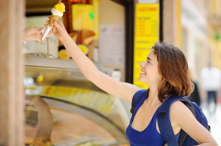 Cheerful girl buys ice cream on the street of Rome. Traditional Italian desserts.