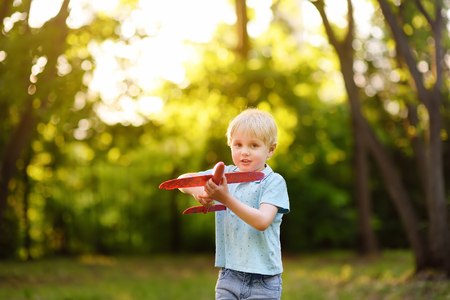 ?ute little boy playing with toy airplane in the sunny park. Kids's fun in the summer outdoors.