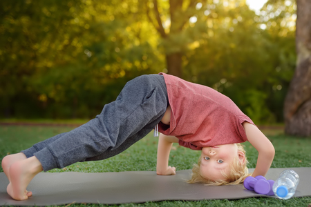 Little boy doing stretch during workout outdoors. Healthy lifestyle for kids. Foto de archivo
