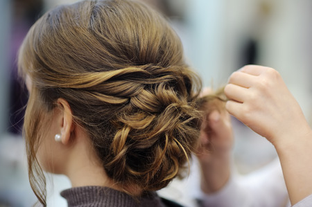 Young womanbride getting her hair done before wedding or party. Wedding or prom ball hairstyles.