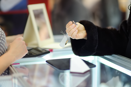 Woman choosing the perfect earrings at a jeweler, close up photo. Focus on your hands.