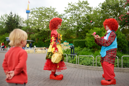 GUNZBURG, GERMANY - MAY 15, 2018: Little boy watches performance funny clowns in LEGOLAND Deutschland at sunny day. Tourism and travel for family with child.