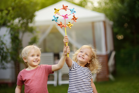 Little boy and girl having fun during walk. Happy child with pinwheel. Preschoolers or toddlers birthday party in summer park.