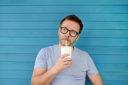 Portrait of a beautiful Mature man drinking a drink outdoors in summer. Party, foods and drinks.