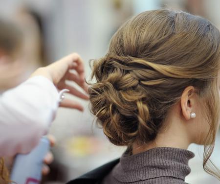 Junge Frau/Braut, die sich vor der Hochzeit oder Party die Haare machen lässt. Hochzeits- oder Ball-Frisuren.