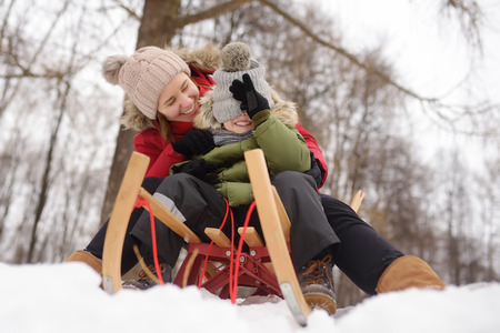 Little boy and mother enjoy sliding on the snow slide. Family winter activities outdoors.