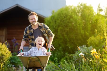Niño feliz divirtiéndose en una carretilla empujando por papá en el jardín doméstico en un cálido día de sol. Juegos activos al aire libre para niños en verano. Foto de archivo