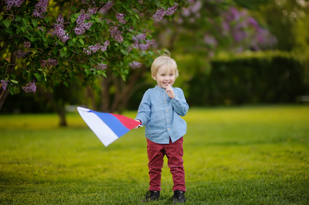 Cute little boy holding russian flag during walking in summer park. Patriotism.
