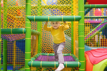 Happy little boy having fun in amusement in play center. Child playing on indoor playground. Active birthday party for preschooler kids.