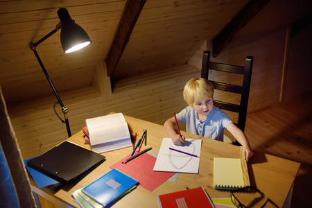 Little boy doing homework, painting and writing at home evening. Preschooler learn lessons - draw and color image. Kid training to write and to read. Child education concept.