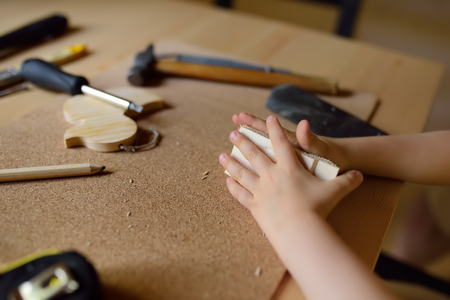 Little boy learns work with tools. Kid make a wooden toy. Close up. Traditional education of boy. Familys values. Dads upbringing. Safety. Stock Photo