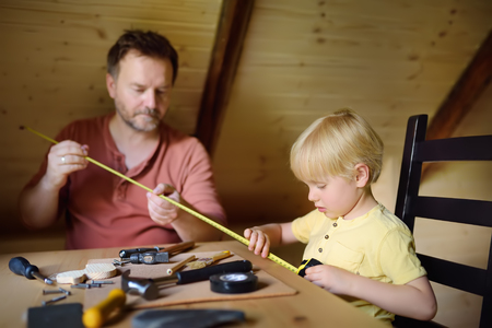 Mature man and little boy make a wooden toy together. Father learn his son work with tools.Traditional education of boy. Familys values. Dads upbringing. Daddys helper. Stock Photo