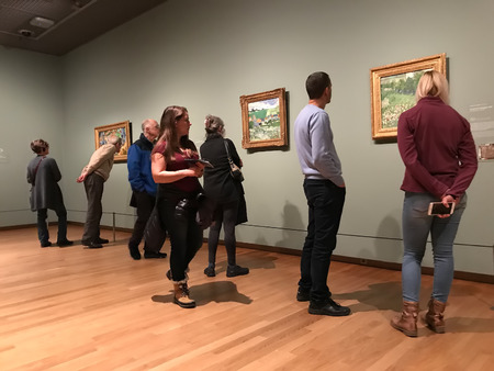 AMSTERDAM, NETHERLANDS - MARCH 19, 2019: Visitors looks at the paintings by Vincent van Gogh in the Museum Van Gogh in Amsterdam, Netherlands. Mobile photo.