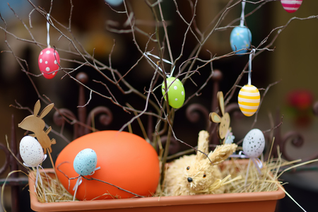 Easter decorations on the street of small town in France. Easter painted eggs hanging on a branch of tree. Catholic holiday.