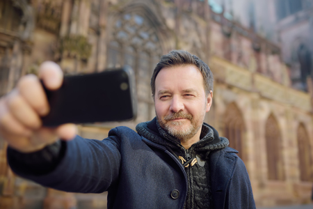 Middle age man making selfie mobile photo with famous Cathedral Notre Dame of Strasbourg on background. Tourist in Strasbourg, Alsace, France