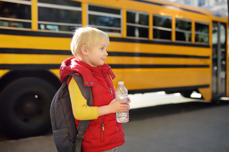 Pupil with schoolbag and bottle of water with yellow school bus on background. Back to school.