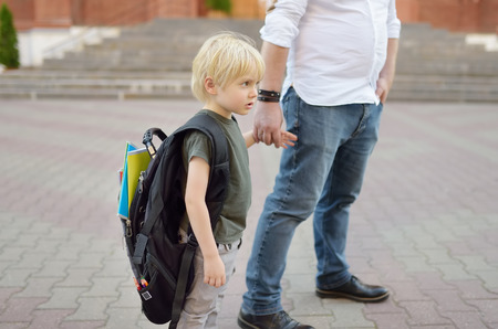 Back to school concept. Little pupil with his father. First day of primary school. Education for small kids.