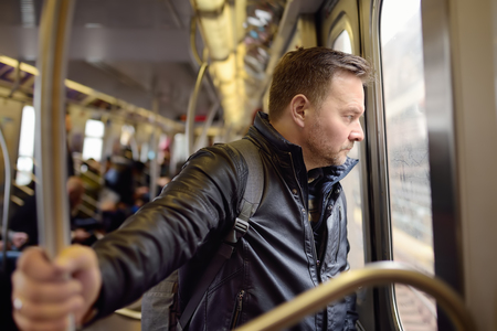 Mature man looks out the window of the car in the subway in new York. Transport of New York. 스톡 콘텐츠