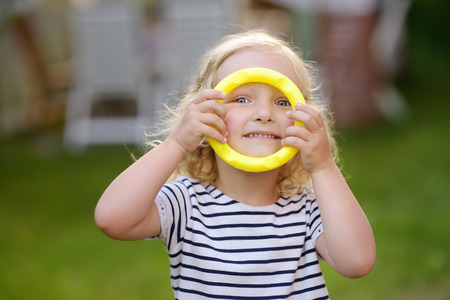 Cute toddler girl outdoors portrait in summer day. Smiling and charming child. Kid playing in game throwing rings at summer outdoors.