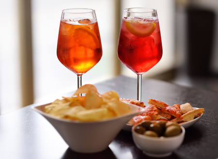 Italian aperitives/aperitif: glass of cocktail (sparkling wine with Aperol) and appetizer platter on the table. Traditional italian cuisine. Imagens