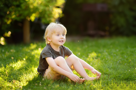 Beautiful boy is sitting on the grass on a sunny summer day. Happy childhood. Children in nature. Stock fotó