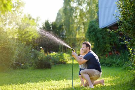 Niño divertido con su padre jugando con una manguera de jardín en el soleado patio trasero. Niño en edad preescolar divirtiéndose con spray de agua. Actividad de verano al aire libre para niños.