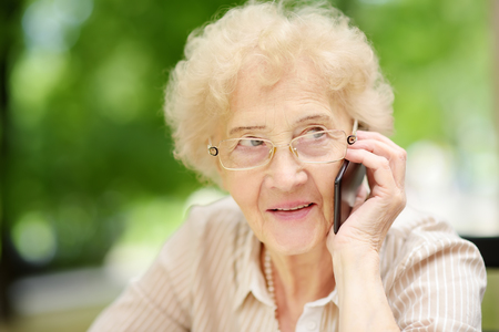 Beautiful senior lady with curly white hair talking on the phone. Communication, talk, gossip. Elderly lady lifestyles. Active longevity concepts.