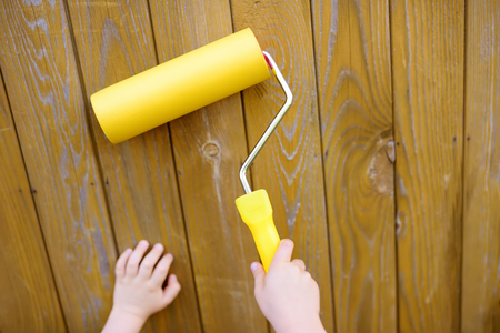 Child paints wooden wall by roller. Hands closeup. Dad's helper.