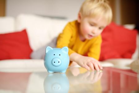 Little boy putting coin into piggy bank. Education of children in financial literacy. 版權商用圖片