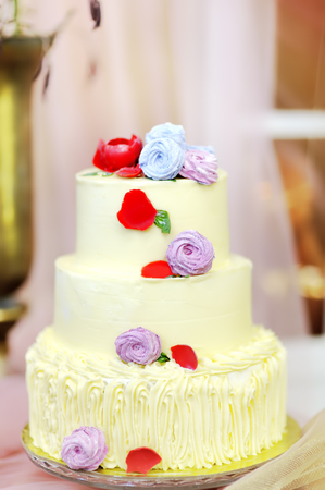 Traditional anniversary/wedding multi-layer cake. Beautiful delicious sweet dessert decorated with flowers on blurred background Imagens