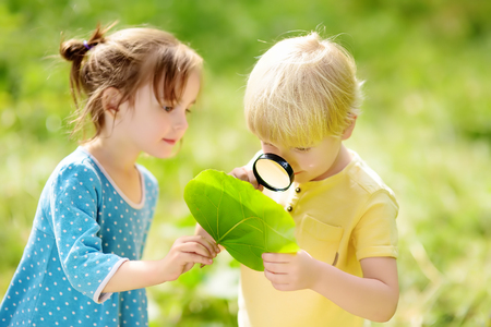 Kids exploring nature with magnifying glass. Close-up. Little boy and girl looking on leaf with magnifier. Summer activity for inquisitive child Archivio Fotografico