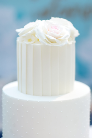 Traditional anniversary/wedding multi-layer cake decorated with flowers. And beautiful delicious sweet dessert on blurred background