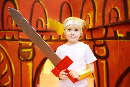 Little boy involved in performance childrens theatre Studio . Child perform kids playing greek heroes on stage in theater. Stock Photo