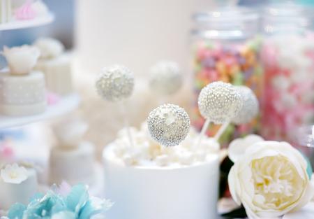 Anniversary/wedding delicious sweet dessert - cupcakes, marshmallow, vanilla cake pops on blurred background. Stylish sweet table.