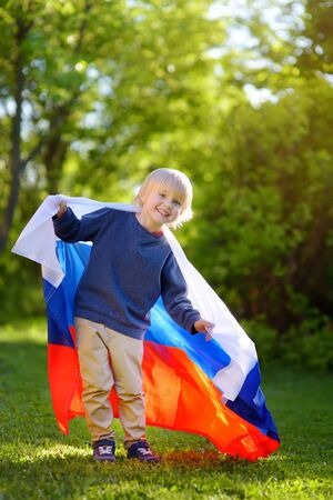Portrait of cute little boy in public summer park with russian flag on background. Fans child supporting and cheering their national team. Day of independence. Pride and patriotism. Banco de Imagens