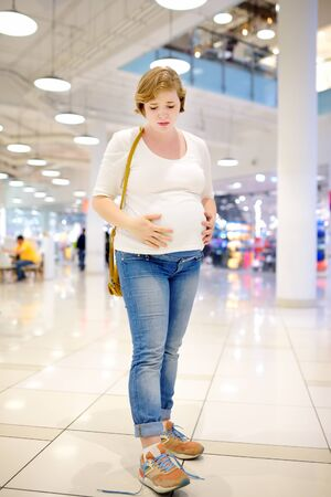 Young pregnant woman in despair because of the untied laceup in the hall of the shopping center. Problems of pregnant women with big belly lace up shoes. Frustrated, desperate, upset, lack of help. Need help.