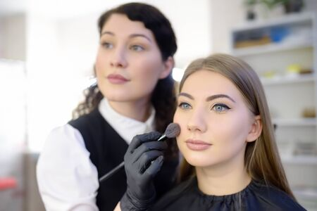 Makeup artist applying the tone of the foundation using special brush on face young beautiful model. Facial care and make up. Professional beauty salon