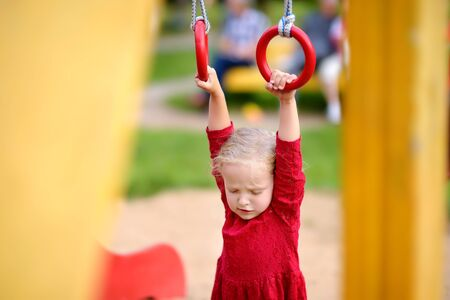 Little girl having fun on outdoor playground. Summer active sport leisure for kids. Kindergarten or school yard. Little child activity Imagens