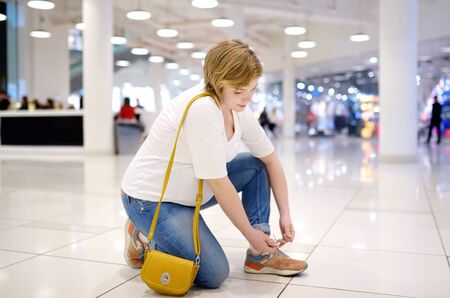 Young pregnant woman lacing up sneakers in hall of shopping mall. Problems of pregnant women with great abdomen lace up shoes. Pregnancy and shopping.