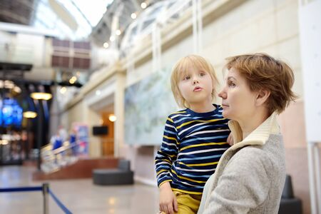 Little caucasian boy and woman looking an exposition in a scientific museum. Education and entertainment for children. Activities for family with preschooler kids.