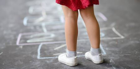 Closeup of little girls legs and hopscotch drawn on asphalt. Child playing hopscotch game on playground outdoors on a sunny day. Summer activities for children.