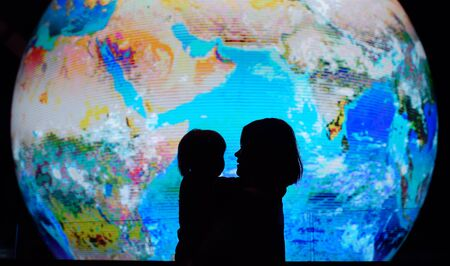 Silhouette of adult and child on background of globe earth. Ecologic and protection environment concept.