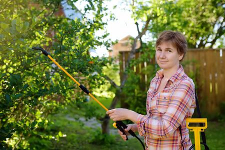 Middle age caucasian woman sprays trees against pests, vermin or diseases plants. Gardening. 写真素材 - 124979036