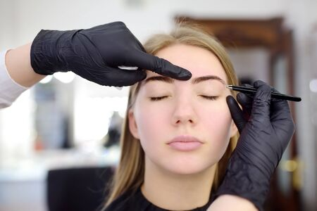 Cosmetologisteyebrow plucking. Attractive woman getting facial care and makeup at beauty salon. Perfect architecture eyebrows. Фото со стока
