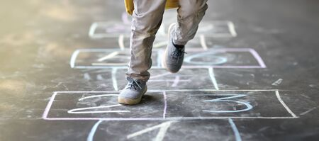 Closeup of little boy's legs and hopscotch drawn on asphalt. Child playing hopscotch game on playground outdoors on a sunny day. Summer activities for children. Archivio Fotografico - 124979283