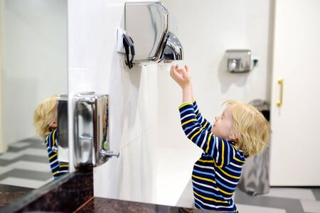 Little caucasian boy drying his hands in a restroom. Hygiene for child. Banco de Imagens - 124979048