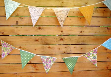 Garland of flags in rustic style on wooden background. Decorative colorful pennants for Holidays party or kids birthday.