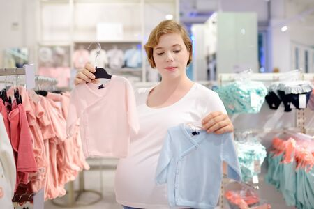 Young pregnant woman choosing pink or blue clothes in the store for newborns. Shopping for expectant mothers and baby. Pregnancy and shopping.