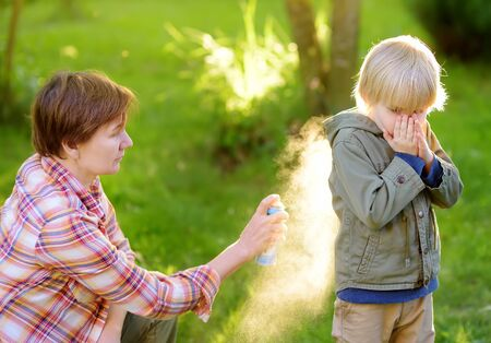 Woman spraying insect or mosquito repellents on little boy before a walk in the forest. Protect children from mosquitoes and other insects. Summer activities for family with child, hiking.