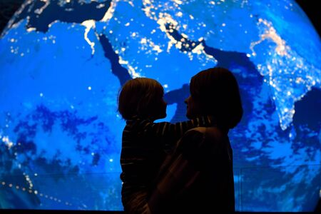Silhouette of adult and child on background of globe earth. Ecologic and protection environment concept. Imagens - 124979080